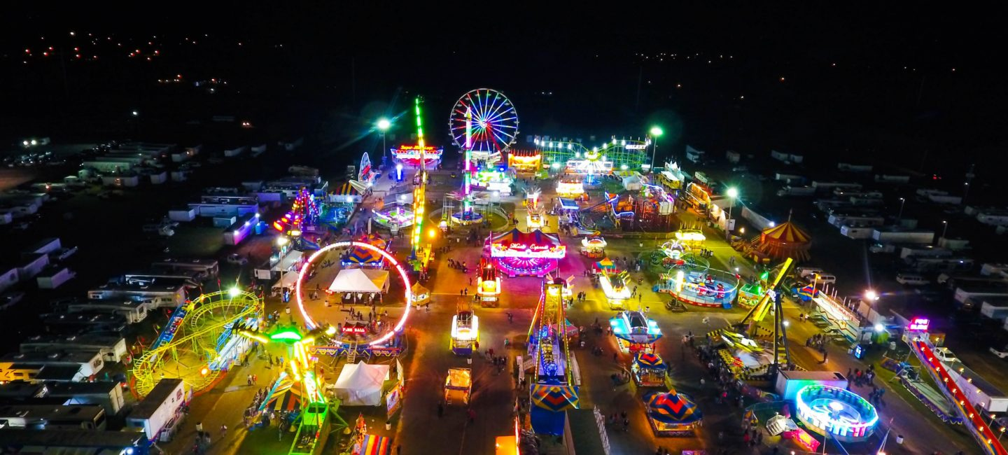 The view looking over a lit up fairground at night