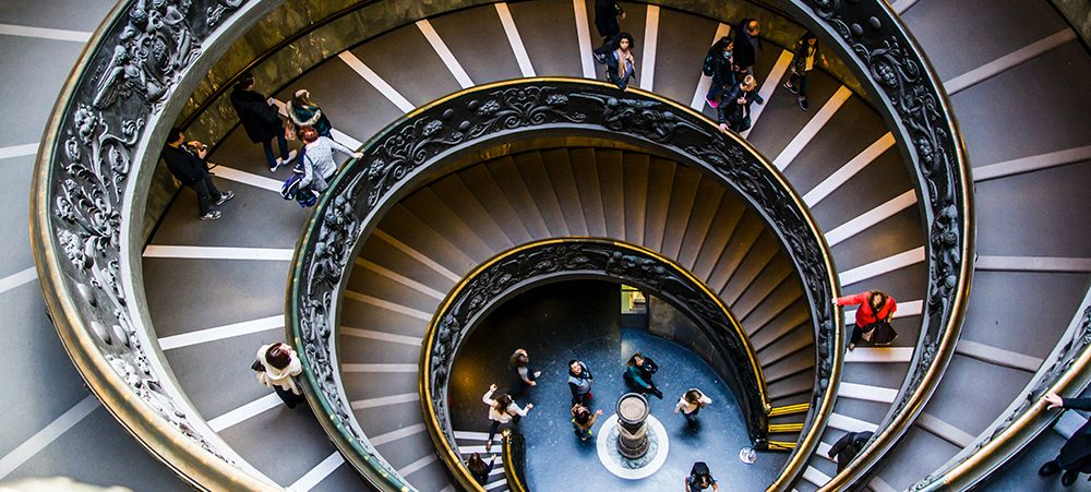 People in a museum walking down a spiral staircase