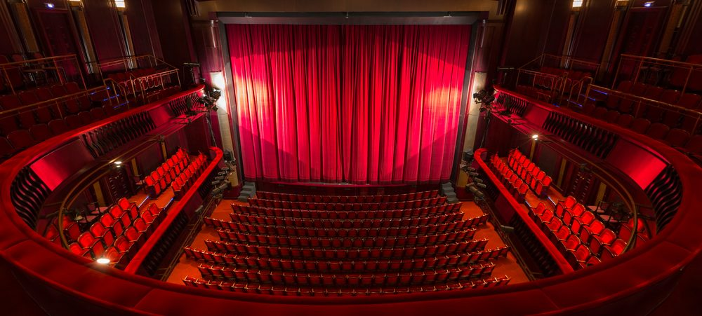 Red curtains closed across a theatre stage